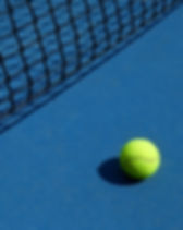 Yellow tennis ball is laying near black