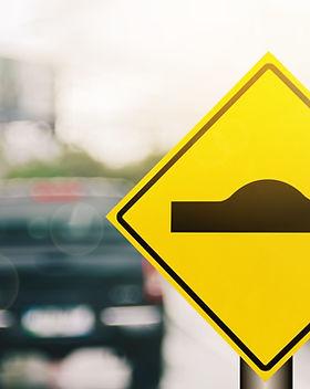 Hump warning sign on blur traffic road w