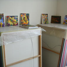 Smaller new paintings stacked on older, larger ones.