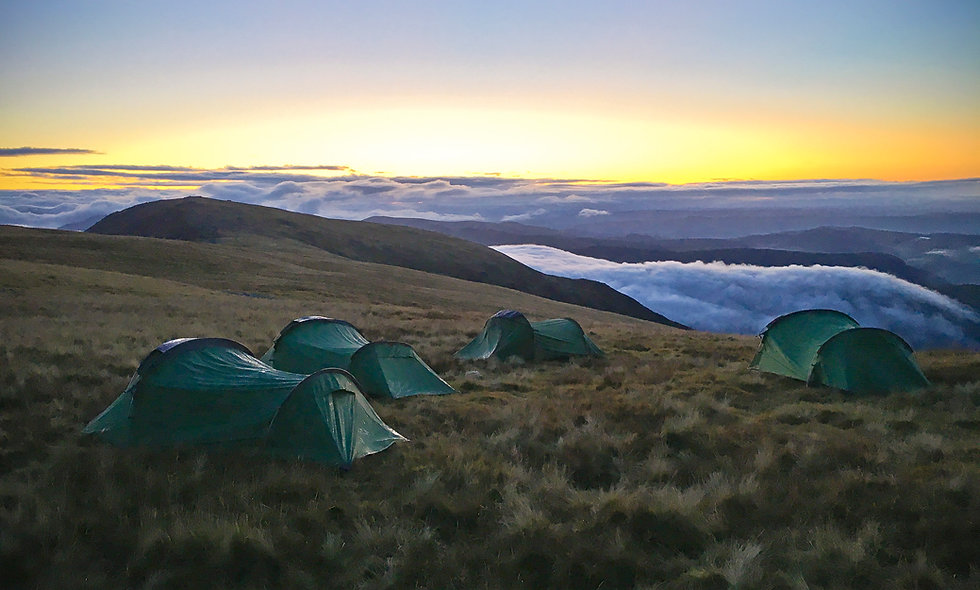 Sunset wild camp on a mountain summit in Snowdonia in Wales
