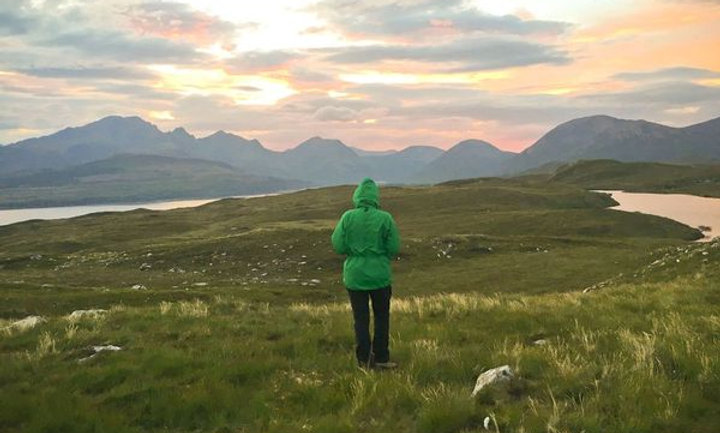 Hiker from London looking at Cuillin Ridge on Isle of Skye at sunset