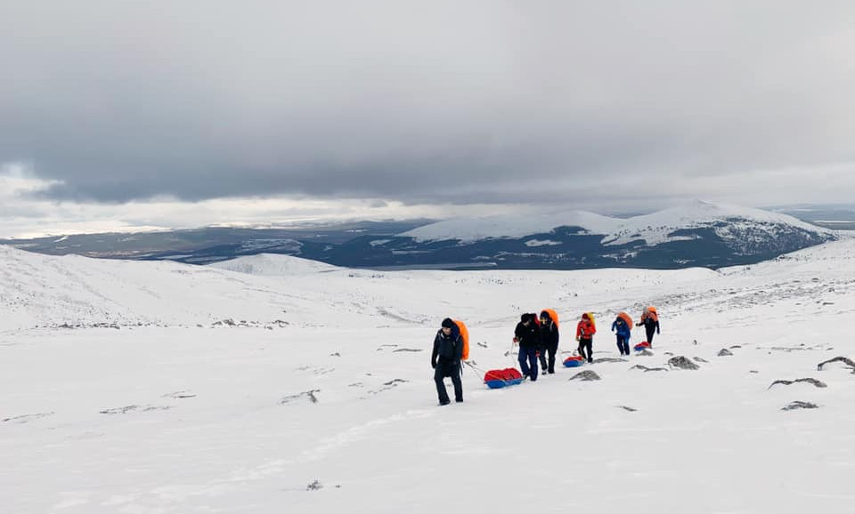Base camp group from London hiking through snow in Cairngorms