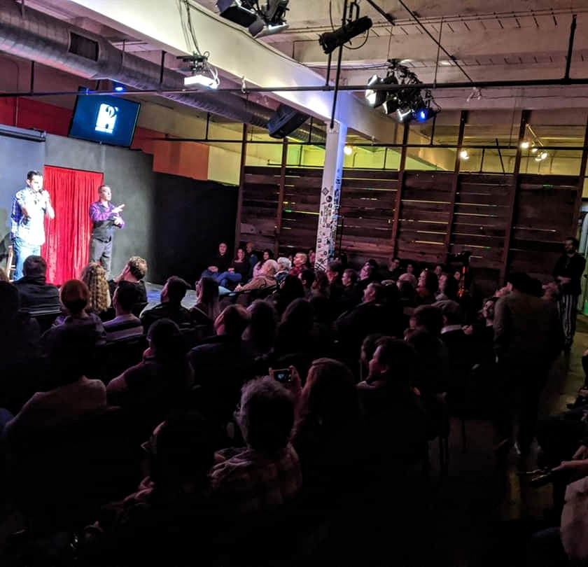 Comedian Robert Vogel performing to a full house audience at the Invisible Disabilities Comedy Show on January 19, 2020 at the Sacramento Comedy Spot. To his right is ASL interpreter Mark Medina of Signs of Pride