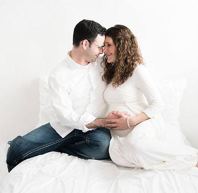 Pregnant Couple Sittin on a Bed Csilla Leonard and Ten Moons Birt