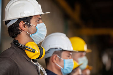Workers wear protective face masks for s