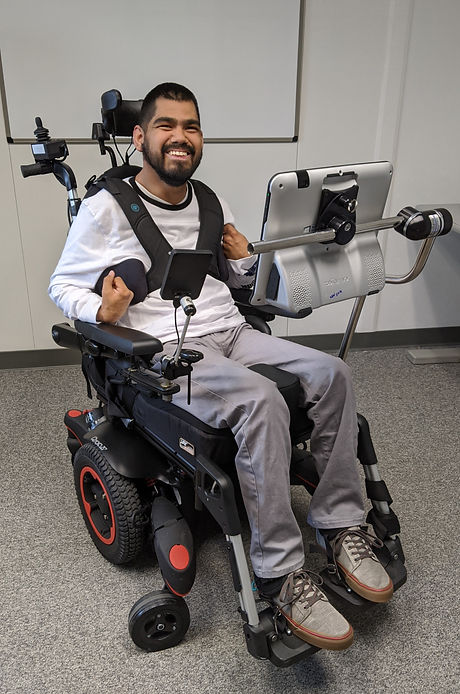 Client in a power wheelchair using a communication device.