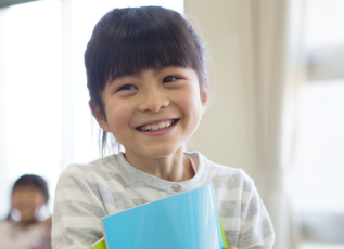 girl smiling with notebook.png