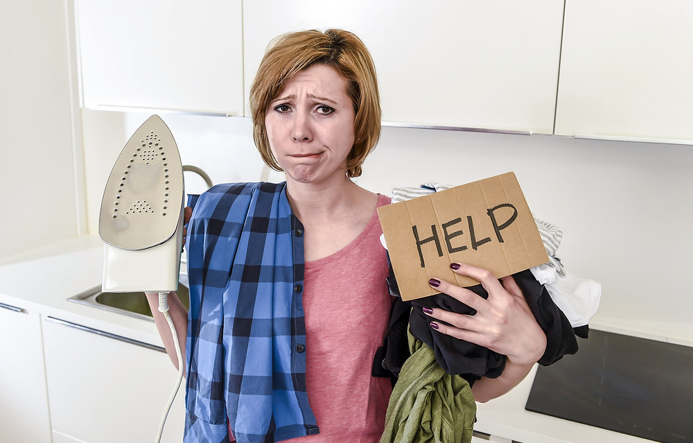 "Stressed woman holding clothes, an iron, and a sign that says ""help""."