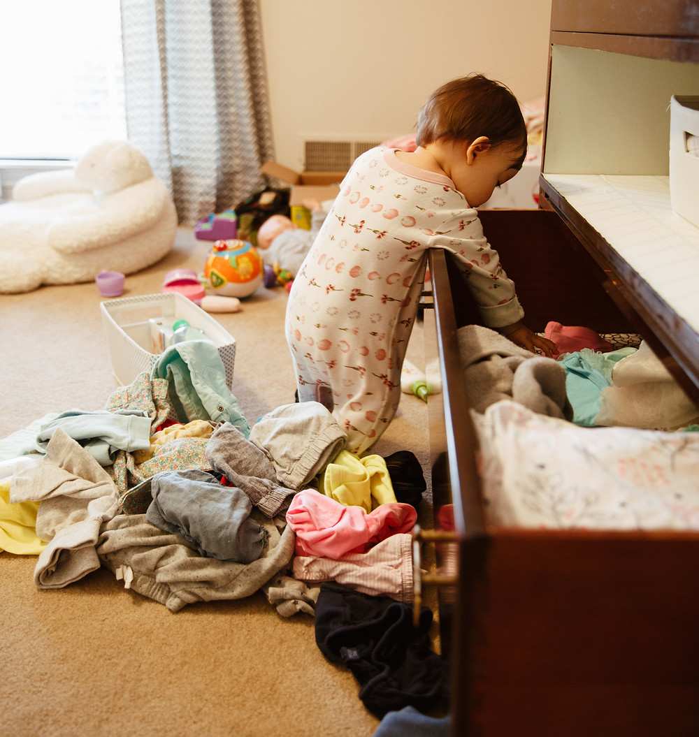 Toddler throwing clothes out of dresser.