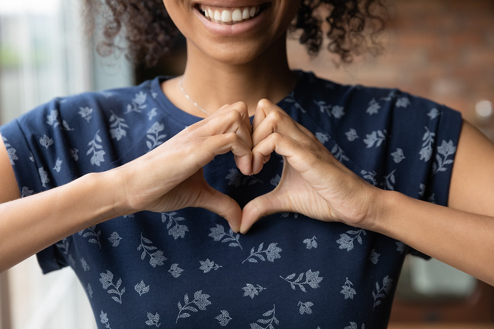 Crop close up of happy African American woman feel grateful thankful show heart sign sprea