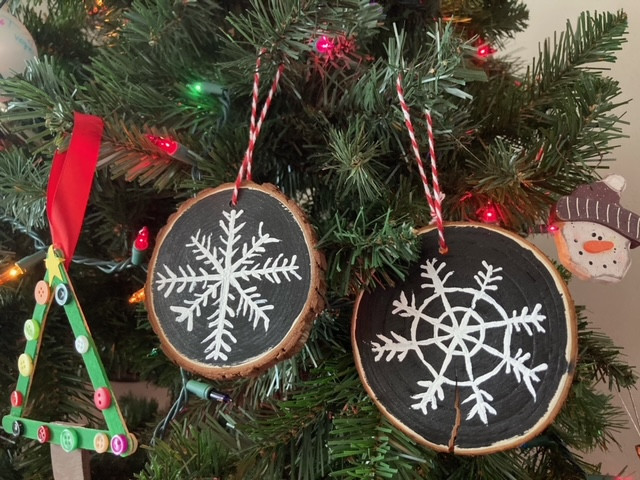 Wood slice ornaments with painted snowflakes hanging on a tree.