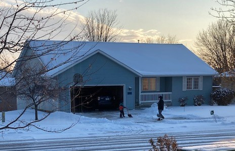My nephew helping a neighbor shovel their driveway.