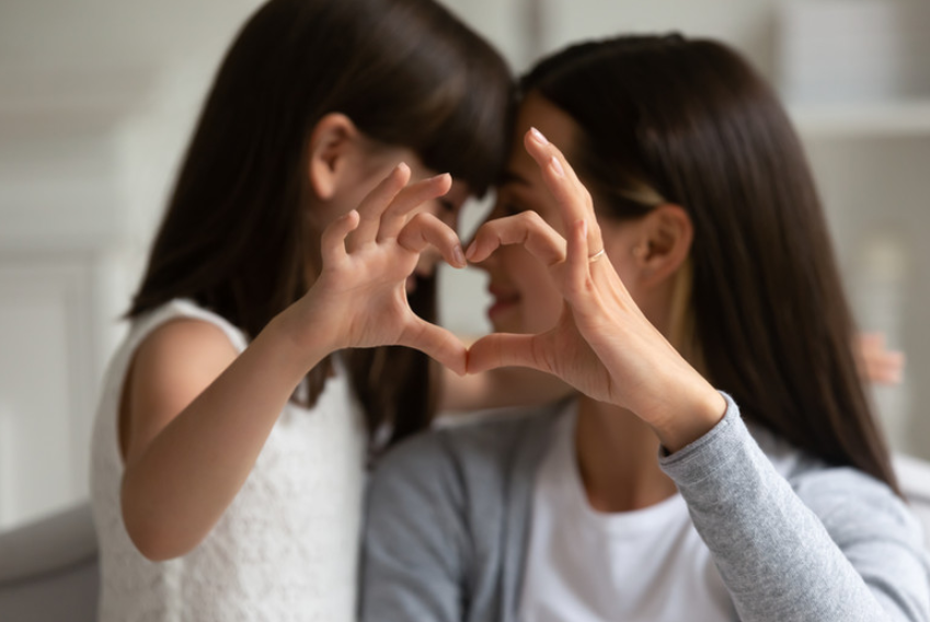 Mother and daughter put hands together in shape of heart
