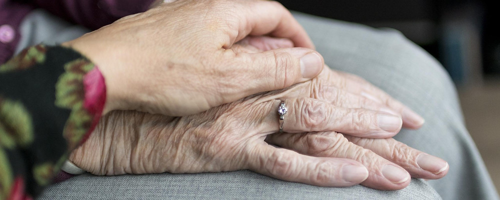 Female hand resting on old woman's hand