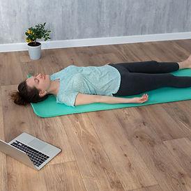 Woman doing Shavasana yoga pose at home