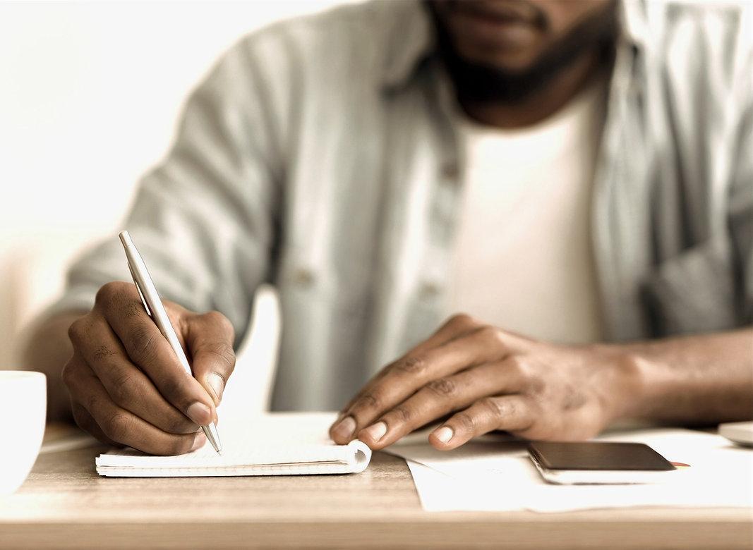 En man skriver ner viktiga anteckningar. Kanske håller han på att lära sig hur man skriver en bok.