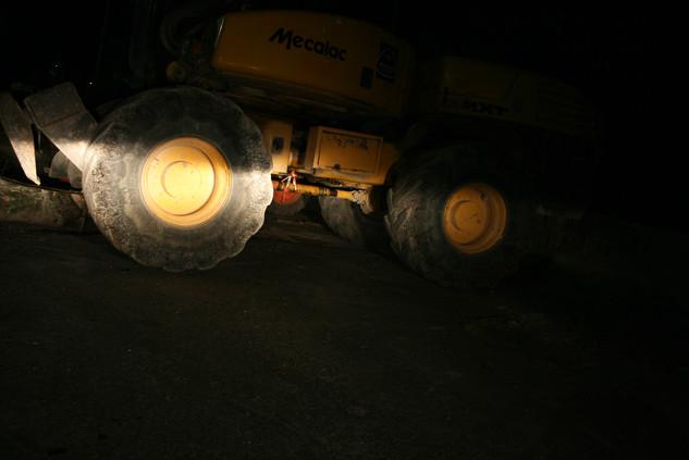 Pelleteuse dont les roues sont éclairées par une voiture dans la nuit