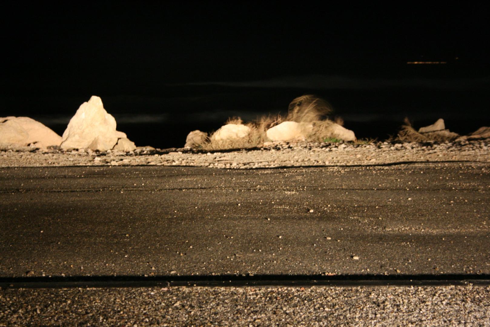 Bord de mer de nuit, roches et graviers éclairés par phares de voiture