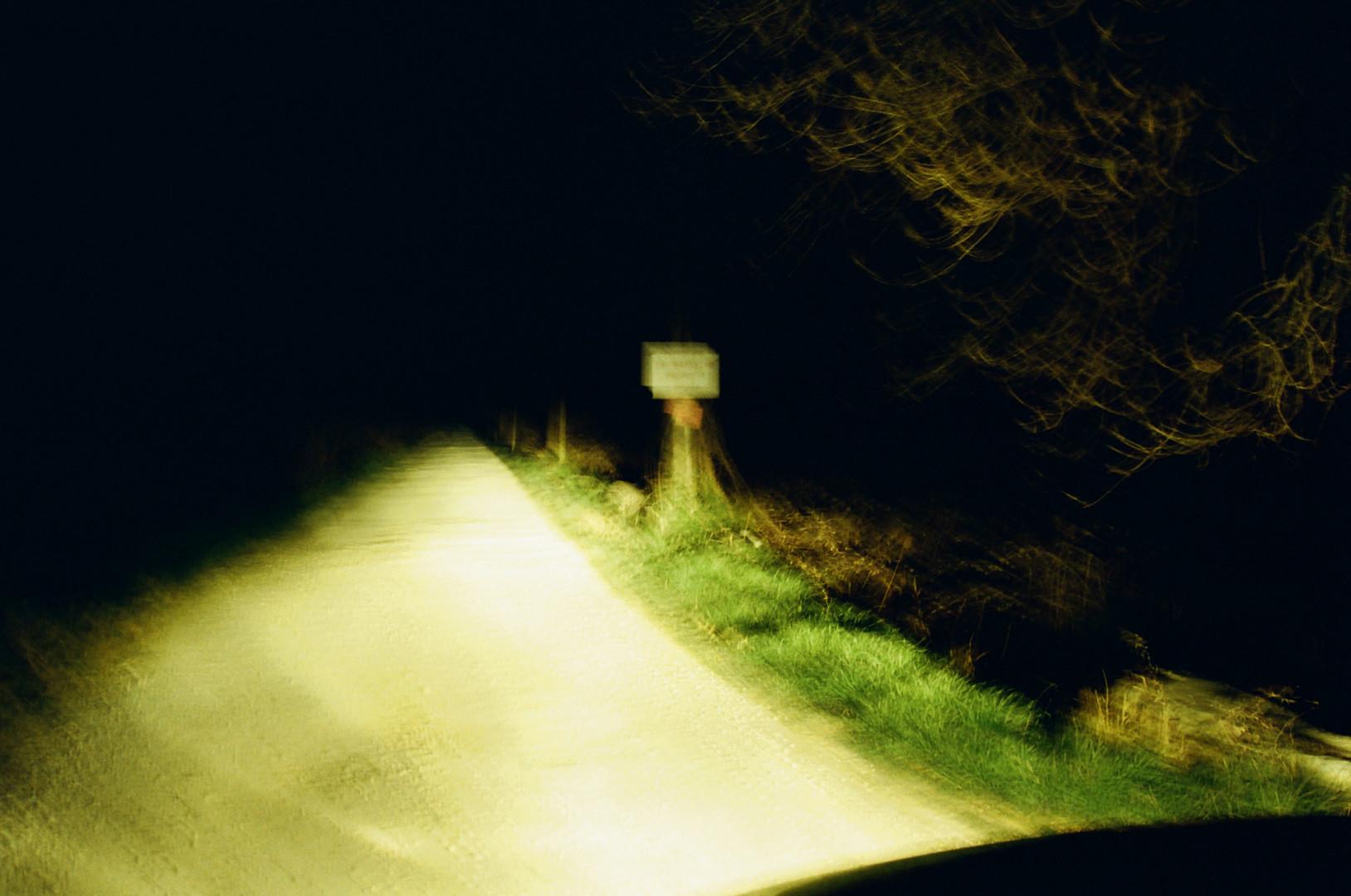 Chemin de campagne éclairé depuis une voiture de nuit, flou