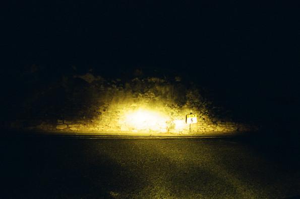Mur éclairé par des phares de voiture la nuit