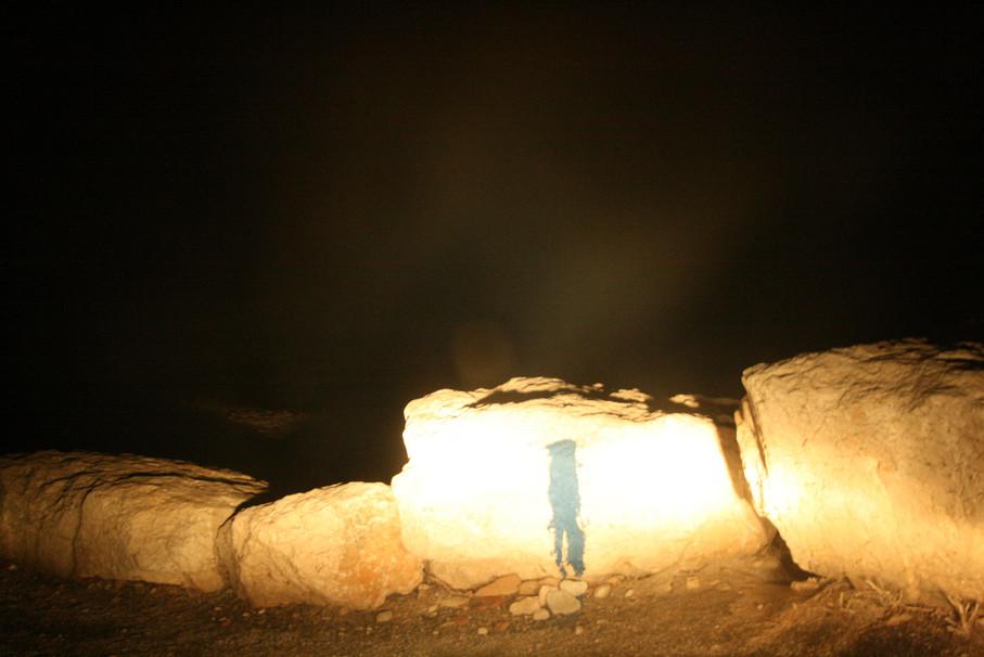 Bord de mer de nuit, rochers avec trace de peinture comme une silhouette éclairés par feux de voiture