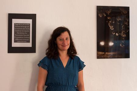 Armelle Mathieu, photographe prise en photo devant ses œuvres photographiques de la salle Le repos, expo Lumières en fuite Marseille 2018