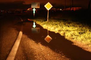 Bord de route avec flaques et avec panneaux routiers herbe et croix éclairé par des phares de voiture