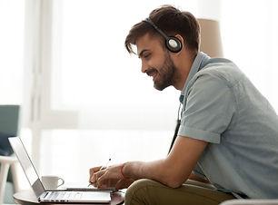 Happy man wearing headset study online l