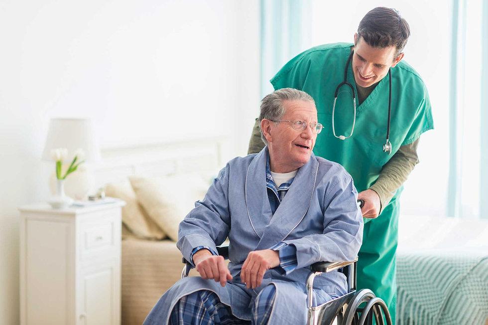 Care worker with elderly man in wheelchair