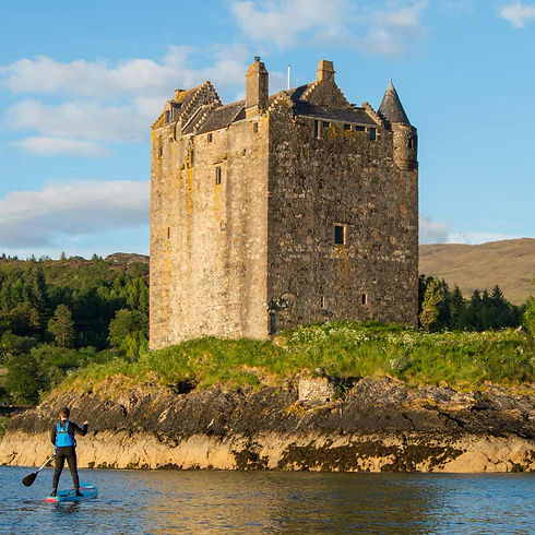 paddle boarder next to castle ruin
