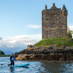 kneeling paddle boarder next to castle r