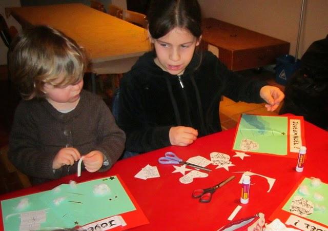 Des enfants appliqués dans la réalisation de leur carte