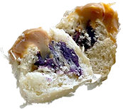 A cut-apart photo of a double filling ensaymada with Yema and Ube fillings