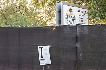A black construction fence in front of a Summer Shade Festival sign.