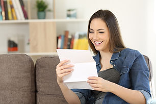 Happy woman reading a letter sitting on
