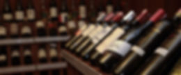 Fox Bros. Liquor department page header with wine bottles on rack