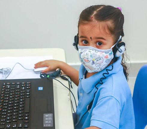 Young preschooler from David & Goliath Preschool does her best at infocomm technology