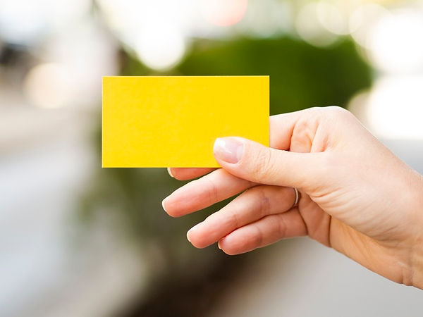 close-up-person-holding-up-yellow-card_2