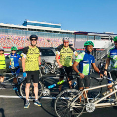 Sherri, Shannon, Mark, Dirk, DJ and Paul all standing in front of their tandems with the Charlotte Motor Speedway grandstands in the background