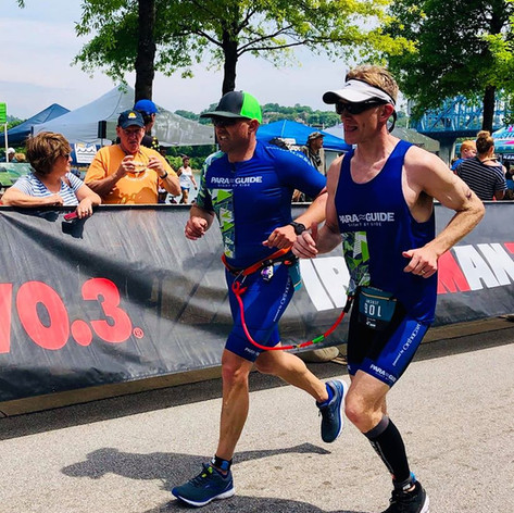 PD: Jeremy and his guide Paul running to the finish line at Ironman Chattanooga 70.3 wearing the Blue and Green Para Guide Triathlon kits