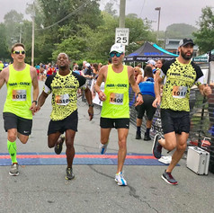 PD: DJ crossing the finish line at the OrthoCarolina 10K with his guides Rick, Tony and Gray wearing their Yellow Para Guide shirts