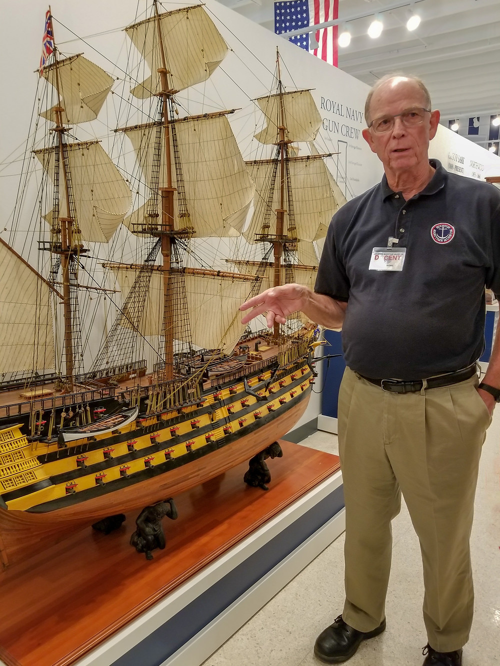 Milt Rose a docent at Houston Maritime Museum stands beside large model ship.
