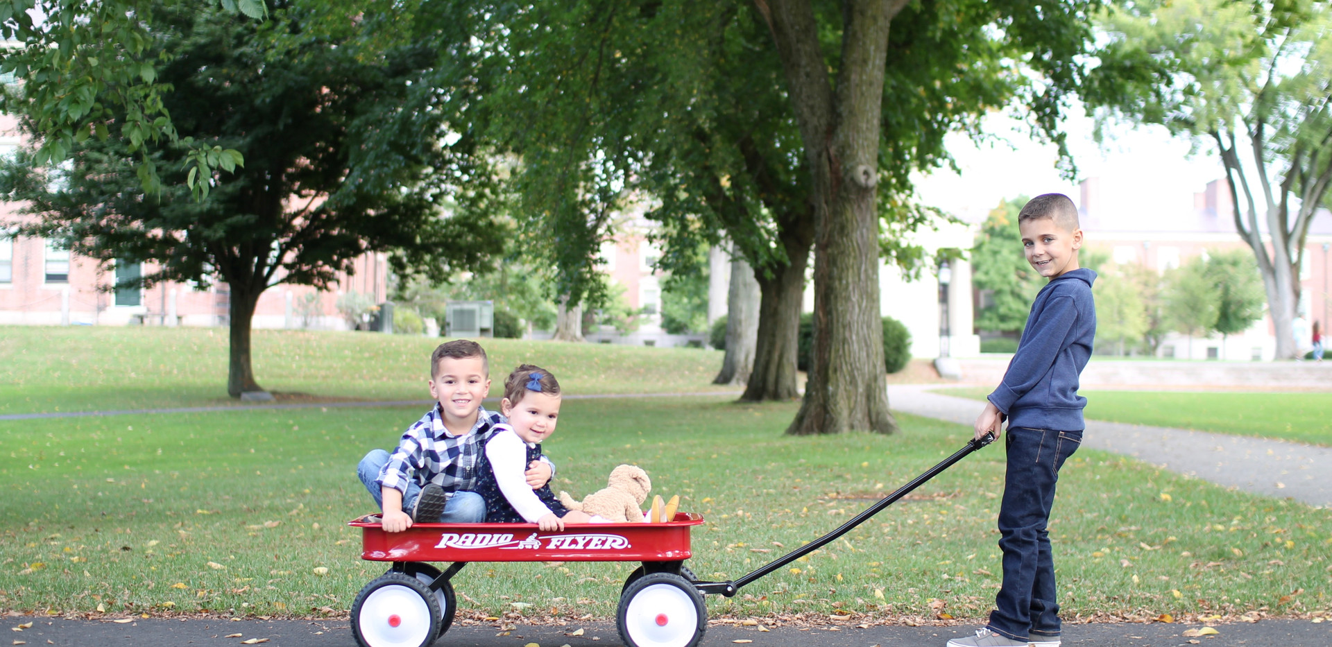 boy puling kids in red wagon, photographer Chattanooga