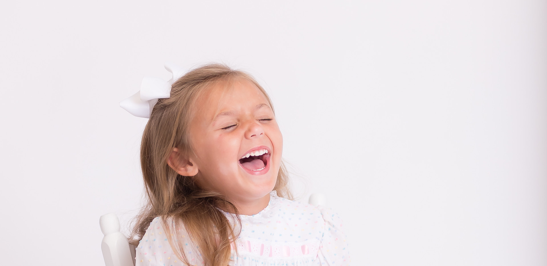 girl laughing, white chair, photographer Chattanooga