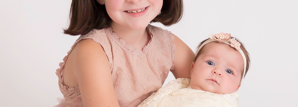 sister smiling with baby, photo studio Chattanooga