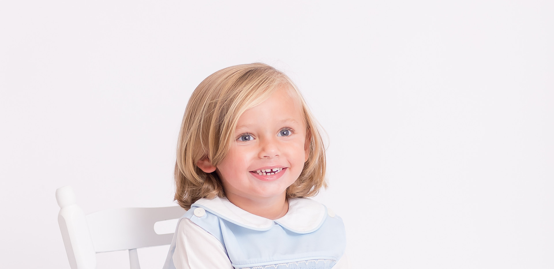 child smiling in white chair, photographer Chattanooga