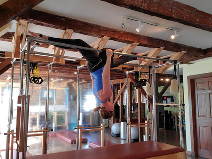 Michelle hanging upside down on the Pilates Cadillac