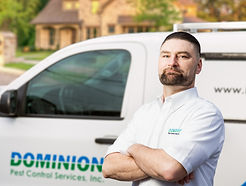 Dominion Pest worker in front of service truck.