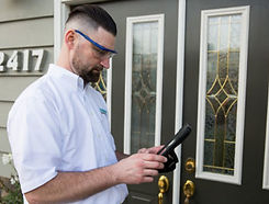 Dominion Pest Control worker with a tablet at a front door.