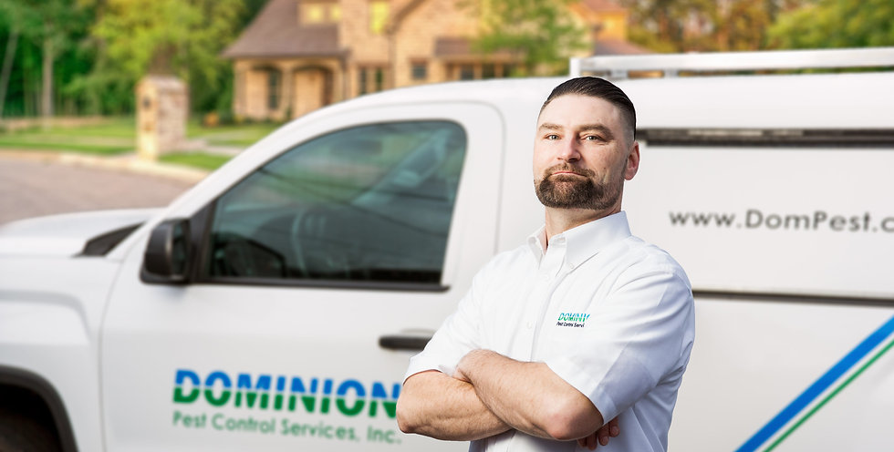 Dominion Pest Control worker in front of service truck.
